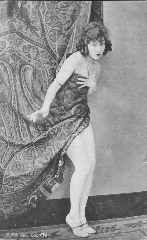 A woman slowly revealing herself naked from behind drapes, vinage 1920's photo
